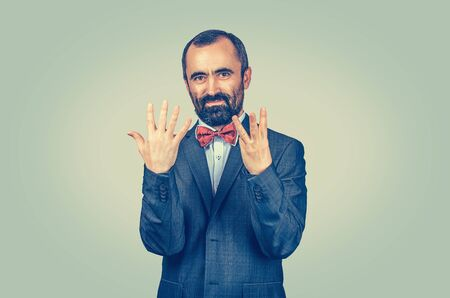 Bearded man show eight fingers gesture with hands isolated green wall background. Facial expression feeling symbol, body language, non verbal communication. Score of competition, number, count, price.