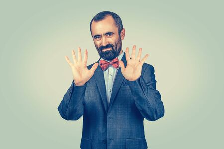 Standing bearded businessman showing his palms showing number ten fingers gesture with hands isolated green background. Symbol, body language, non-verbal communication. Innocence, incorruptible honest