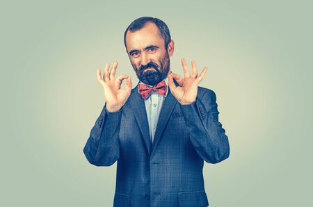 Confident bearded businessman showing ok sign with both hands, fingers isolated on green wall background. Human emotion, face expression, symbol, body language, non-verbal communication of excellence