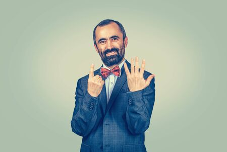 Portrait smiling, happy bearded man showing 6 fingers, giving number six sign, the sixth isolated on green yellow background. Positive human emotion face expression, body language. Score.