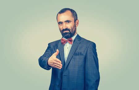 Serious, bearded businessman is going to give a handshake isolated on green. Agreement, welcome. Confident, standing man with dark suit, blue shirt, red bow, tie, looking to you camera. Human gesture