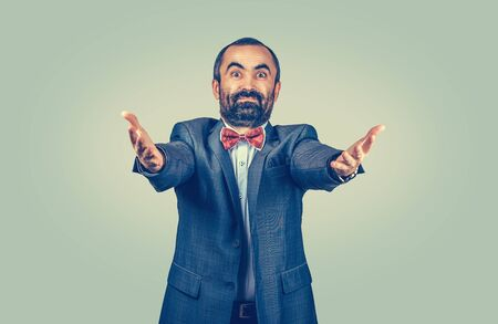 Standing, happy, bearded businessman asking what did you do, come here and hug me, looking camera. Isolated uniform gradient green yellow wall background. Human emotions face expressions body language. Banco de Imagens