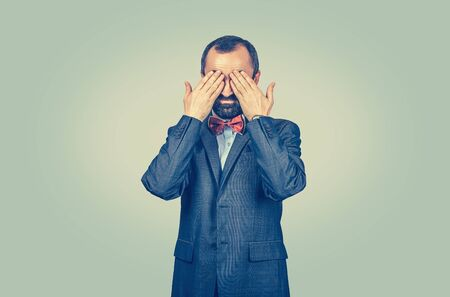 Bearded businessman covering his eyes with his hands. Isolated, half length body, light green yellow background. Human emotions face expressions body language