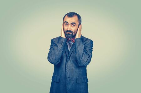 Astonished, bearded businessman covering his ears with hand palms isolated on light green yellow wall background. Facial expressions, feelings, body language, life perception.