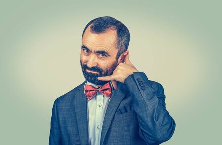 Closeup portrait bearded businessman, handsome worker making showing call me gesture sign with hand shaped like phone,isolated green yellow wall background. Human emotion face expression body language Banco de Imagens