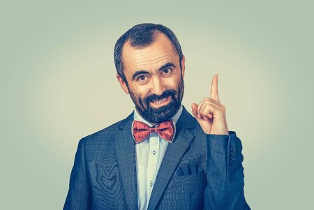 Attention. Elegant bearded businessman pointing upwards and looking at camera isolated on light green yellow background. Gesture facial expression symbol, body language, non-verbal communication
