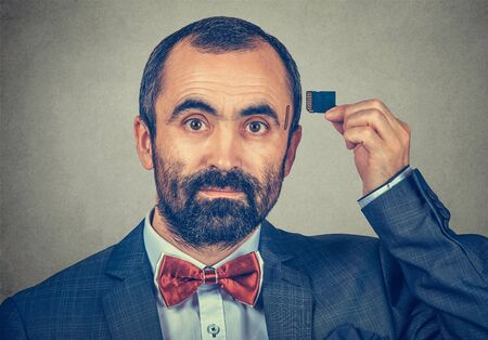 External memory needed concept. Portrait of a serious bearded businessman wearing elegant jacket and red bow tie holding Micro SD card near his head isolated on grey background. Human face expression  Banco de Imagens