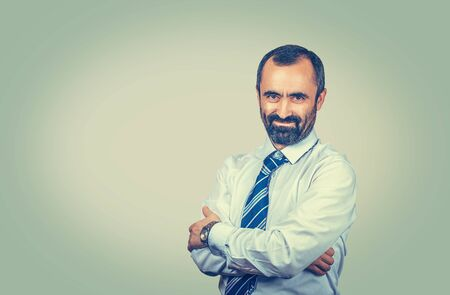 Dark brown haired bearded man with blue tie and white shirt. Crossed arms. Smiling raillery employer looking to you camera. Positive gentleman with watch isolated on light green yellow background. Banco de Imagens