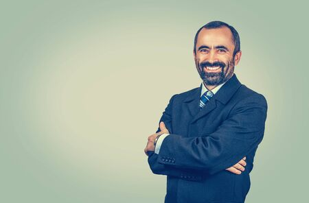 Bearded man with suit tie, blue shirt red bow tie. Crossed arms. A smiling employer looking at you camera isolated on light green-yellow background. Positive human emotion facial expression feeling. Banco de Imagens