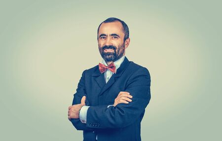 Successful, confident bearded man with dark suit, blue shirt, red bow tie, looking to camera isolated on green-yellow background. Elegant manager with crossed arms. Positive emotion, Body expression