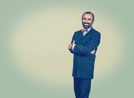 Happy businessman standing with crossed arms isolated on green yellow background. Smiling bearded man with dark suit, blue shirt, red bow tie, looking at you camera. Elegant clothes. Positive emotion