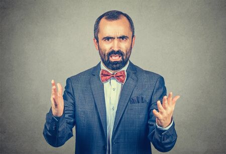 Angry young business man screaming hands in air in frustration looking at you camera mad. Mixed race bearded model isolated on gray background with copy space. Horizontal image