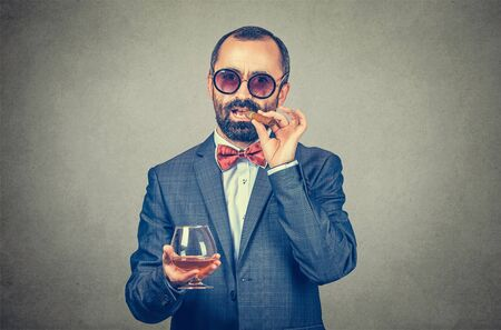 Like a boss concept. Closeup portrait of a confident businessman holding about to smoke a cuban cigar and a glass of wine wearing sunglasses. Mixed race bearded model isolated on gray background