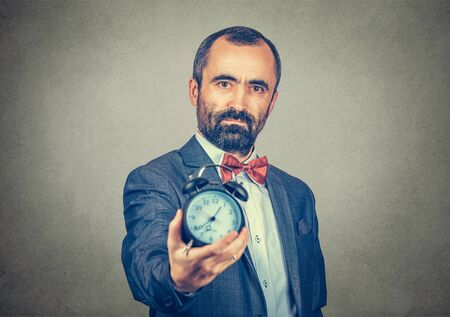 Portrait of a businessman office manager, man in formal clothing holding showing alarm clock, deadline concept. Mixed race bearded model isolated on gray background with copy space. Horizontal image. Banco de Imagens