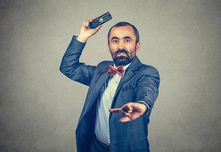 Halbes Körperlängenporträt eines Mannes, der eine TV-Fernbedienung wirft und Ihre Kamera verängstigt und wütend ansieht. Gemischtes bärtiges Modell auf grauem Hintergrund mit Kopienraum isoliert. Horizontales Bild.