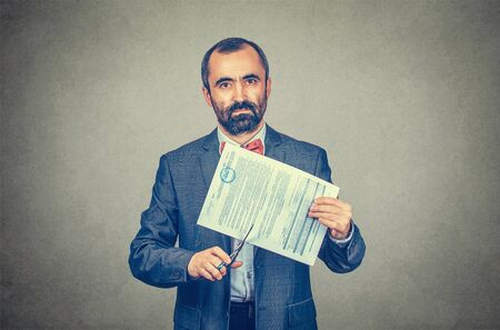 Image of man cutting a document with scissors while looking at you camera serious. Cancel a contract concept. Mixed race bearded model isolated on gray background with copy space. Horizontal image