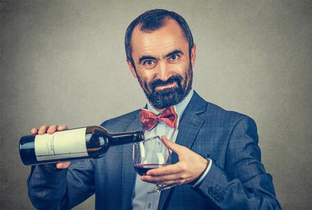 A man pours some wine into a glass from a bottle looking at you camera smiling. Mixed race bearded model isolated on gray background with copy space. Horizontal image. Winemaker analyzing wine concept Banco de Imagens