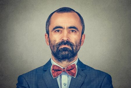 portrait of handsome hipster mature businessman with beard looking at you with serious and confident face expression. Mixed race bearded model isolated on gray background with copy space. Horizontal