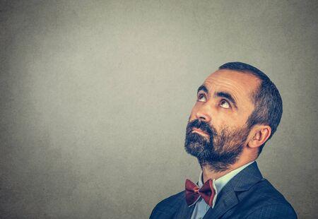 Kopfschuss verwirrter Mann, der denkt, zur Seite zu schauen, die interessiert ist, einzeln auf grauem Hintergrund mit Kopienraum über dem Kopf für Ihren Text oder Ihr Design. Menschlicher Gesichtsausdruck Emotion Körpersprache