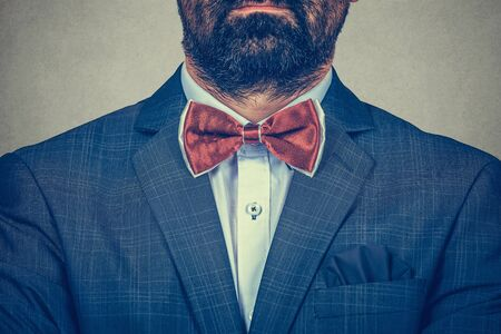 Groom style concept. Masculine blue navy suit, red Bow tie, white shirt. Formal clothing cropped image with no face, just the beard and shoulders of a stylish man on gray background. Horizontal image