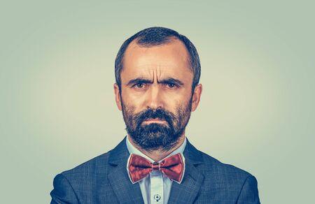 Homme sérieux snuffy agacé regardant la caméra malheureux. Modèle barbu de race mixte isolé sur fond jaune vert avec espace de copie. Image horizontale. Banque d'images