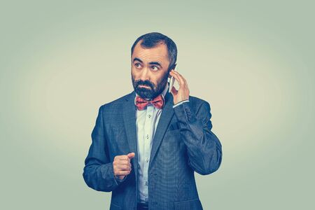 Businessman talking on a mobile phone listening to his voice messages with a serious expression on face. Mixed race bearded model isolated on green yellow background with copy space. Horizontal image