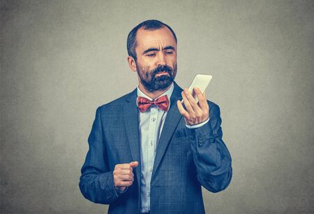 Businessman with a mobile phone reading a message with a serious expression. Mixed race bearded model isolated on gray background with copy space. Horizontal image