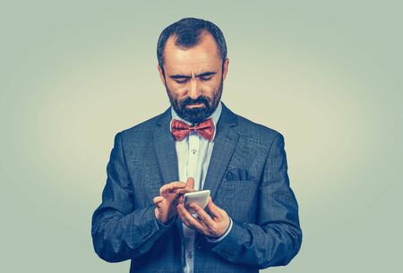Businessman using browsing through new smartphone, connected to world wide web internet. 4g 5g data plan provider. Mixed race bearded model isolated on gray background with copyspace. Horizontal image Banco de Imagens