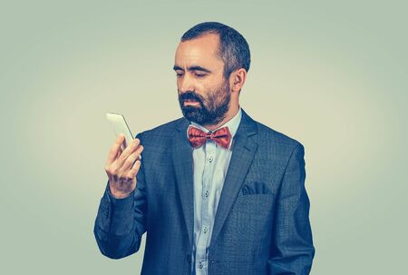 Businessman with a mobile phone reading a message with a serious expression. Mixed race bearded model isolated on green yellow background with copy space. Horizontal image