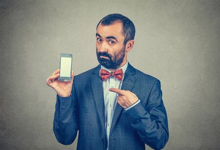 Portrait closeup of man showing phone screen pointing at it with index finger, seller proposing cell to a client. Mixed race bearded model isolated on gray background with copyspace. Horizontal image