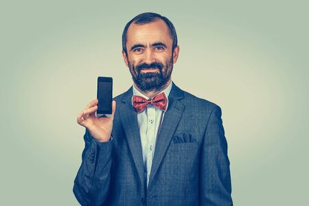 Young caucasian businessman looking at you camera showing smartphone screen. Mixed race bearded model isolated on green yellow background with copy space. Horizontal image.