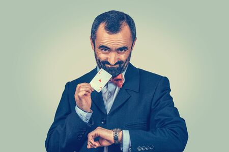 Bearded businessman showing ace card and watch, looking sly to you camera. Win now. Right time for business, take decision. Gambling concept. Opportunity, luck, chance. Isolated green wall background
