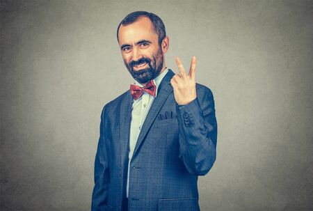 Portrait headshot middle aged businessman smiling with victory hand sign symbol isolated grey wall office background. Positive emotion face expression body language gesture attitude. Success concept
