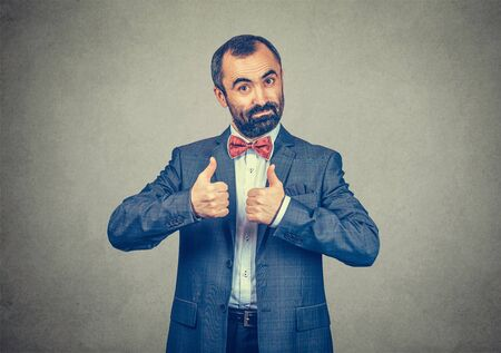 Happy man giving thumbs up sign like hands gesture. Hipster male with beard in blue plaid checkered shirt  Isolated on gray studio Background. Negative face expression, human emotion, body language.