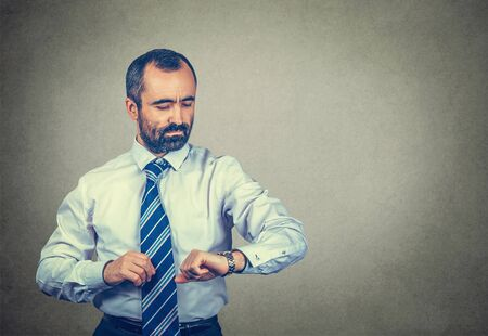 Calm middle-aged man looking at his wristwatch attentively, checking the time to not be late to a meeting. Mixed race bearded model isolated on gray background with copy space. Horizontal shot