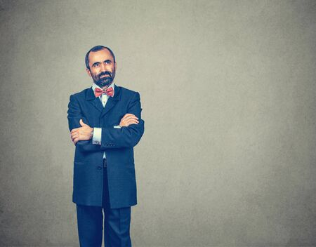 Thinking. Bearded man in formal clothing looking up to the side copy space. Expressive positive face. Crossed arms. Mixed race bearded model isolated on gray studio wall background. Horizontal image. Banco de Imagens