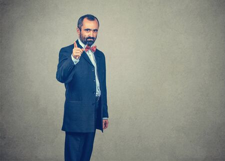 Portrait of an angry middle-aged man in formal wear pointing finger at you camera with anger gesture. Mixed race bearded model isolated on gray studio wall background with copy space. Horizontal image
