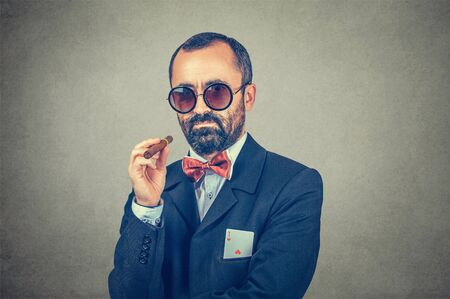Ace card under sleeve - business man. Serious bearded boss in sunglasses, holding a cigar in hand with ace in his pocket isolated on gray background. Secret. Success, winner. Backup strategy concept.