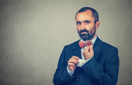 Closeup portrait middle-aged man deal maker pulling out a hidden ace card from the suit jacket sleeve looking at you camera serious. Mixed race bearded model isolated gray background with copy space