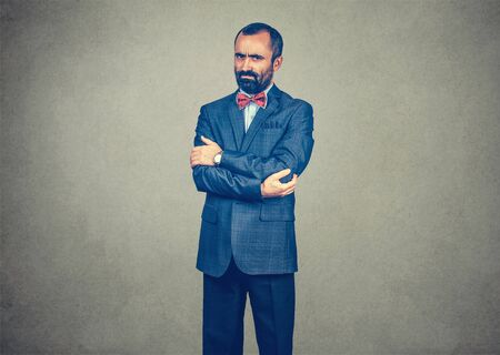 Businessman, man in suit standing looking serious cranky arms crossed. Mixed race bearded model isolated on gray studio wall background with copy space. Horizontal image.