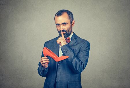 Shh. Sly bearded businessman man holding a red shoe, making silence gesture with hand looking at camera. Mixed race bearded model isolated on gray studio background. Confidentiality, business secret