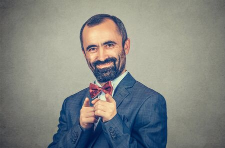 Closeup portrait of man in suit, smiling businessman pointing at you camera with both index fingers. Mixed race bearded model isolated on gray studio wall background with copy space. Horizontal image 版權商用圖片
