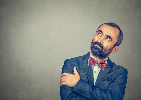 Portrait thinking handsome man pensive looking up to the right side. Mixed race bearded model isolated on gray studio wall background with copy space. Horizontal image. Banco de Imagens