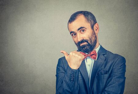 man in suit, businessman shows the direction pointing finger to side copy space looking to the camera convincing that is the right direction to go. Mixed race bearded model isolated on gray background