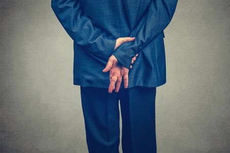 Swearing an oath with fingers crossed behind the back, concept for dishonesty or business fraud. Model blue navy suit with, cropped body isolated on gray studio wall background with copy space