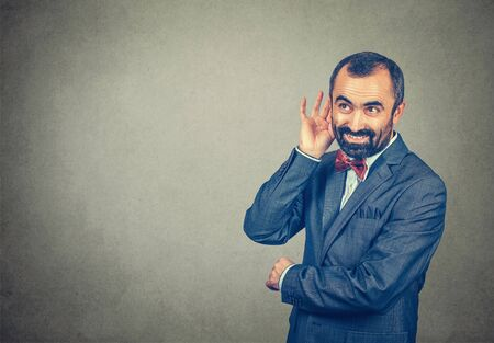 man eavesdropping smiling happy, businessman with his hand to his ear trying to listen smiling happy. Mixed race bearded model isolated on gray studio wall background with copy space. Horizontal image