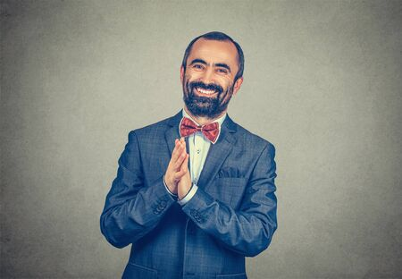 Portrait of Satisfied businessman smiling man with clasped hands looking at you camera happy. Mixed race bearded model isolated on gray studio wall background with copy space. Horizontal image.