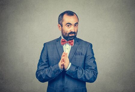 Businessman explaining something, saying look, listen, I have to tell you something hands gesture and body language. Man looking at camera interested Mixed race bearded model on gray studio background