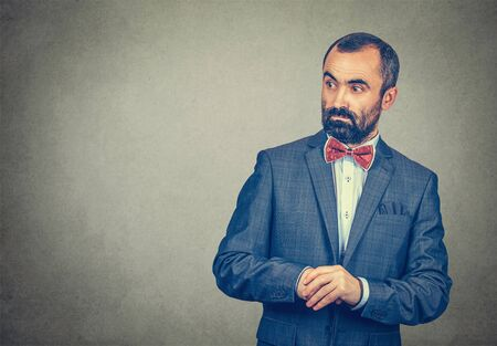 Businessman looks worried surprised, shocked, stunned to the side blank copy space. Mixed race bearded man, model isolated on gray studio wall background with copy space. Horizontal image.
