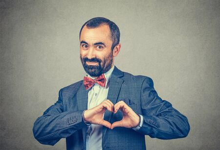 businessman showing heart shape with hands looking at you camera smiling happy. Love, care passion concept. Mixed race bearded model isolated on gray background with copy space. Horizontal image.